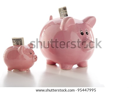 Close-up of two piggy banks, one little one and one large one, isolated on white