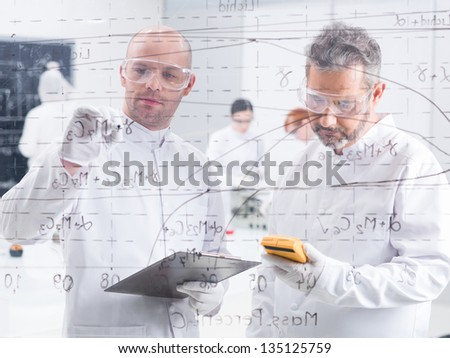 close-up  of two researchers in a lab writing formulas on a transparent board and scanning results with another two student in the background - stock photo