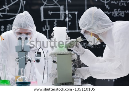 close-up   of two scientists analyzing under microscope in a chemistry lab with a blackboard on the background - stock photo