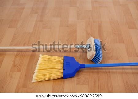 closeup of two sweeping brooms on wooden floor