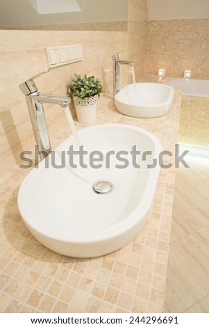 Close-up of two washbowls with running water - stock photo