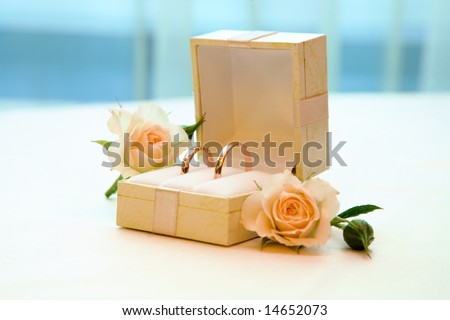 Close-up of two wedding rings in box with roses near by - stock photo