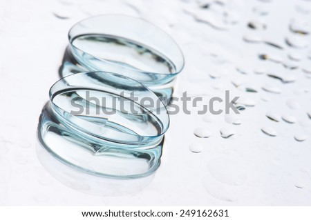 Close-up of two wet soft contact lenses with reflection on light background with drops and copy space. Shallow DOF. - stock photo
