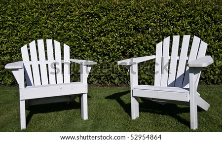 Close up of two white adrindack chair on a lawn. - stock photo