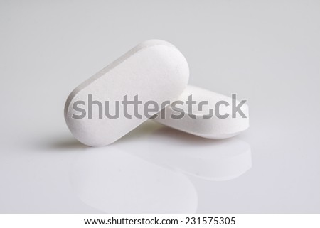 Close-up of two white pills on white background  - stock photo
