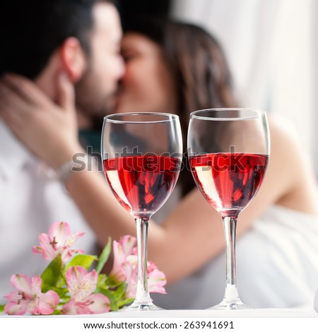 Close up of two wineglasses with rose wine and flower bouquet.In background a out of focus couple kissing.