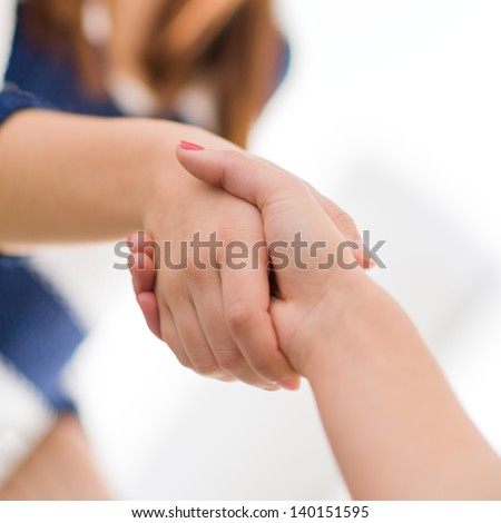 Close Up Of Two Women Shaking Hands, Indoors - stock photo