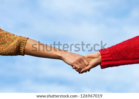 Close up of two young adults holding hands against the blue sky. - stock photo