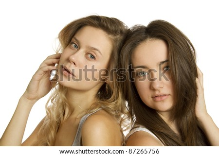Close-up of two young attractive women blonde and brunette. Isolated on white background