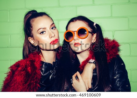 Close-up of two young cheeky fashion girls posing on a background of green brick wall