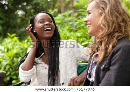 Close-up of two young female friends gossiping in park - stock photo