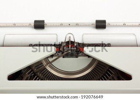 Close-up of typewriter with typebar striking ribbon; with blank sheet of paper. Space for copy. - stock photo