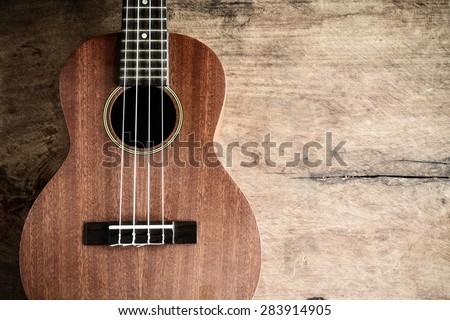Close up of ukulele on old wooden background, Dark tone