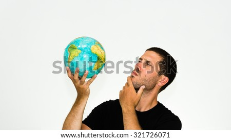 close-up of undecided caucasian man observing a world globe in his hand - conceptual image isolated on white background with copyspace