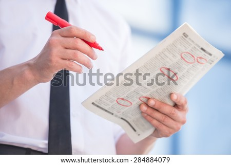 Close-up of unemployed man in suit reading newpaper outdoors. - stock photo