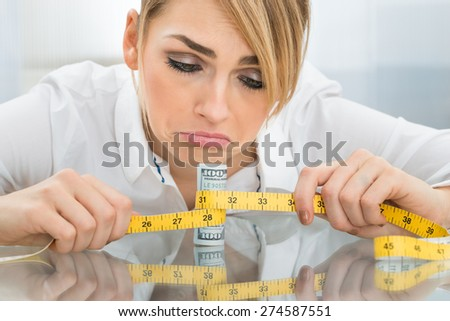 Close-up Of Unhappy Businesswoman With Measuring Tape Around Dollar Banknote - stock photo
