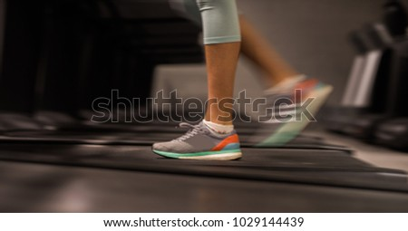 Close up of unknown female running on treadmill in gym. Healthy lifestyle, warming up before sport training, fitness, pilates, cross training or yoga.
