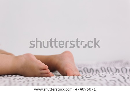 Close-up of unrecognizable baby lying barefoot on patterned bedsheet
