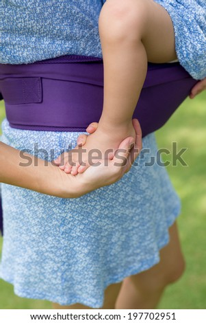 Close-up of unrecognizable lady carrying her little daughter - stock photo