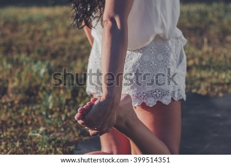 Close-up of unrecognizable woman stretching her leg while standing on lawn in sunlight - stock photo