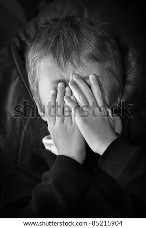 Close-up of upset child's hands and face. - stock photo