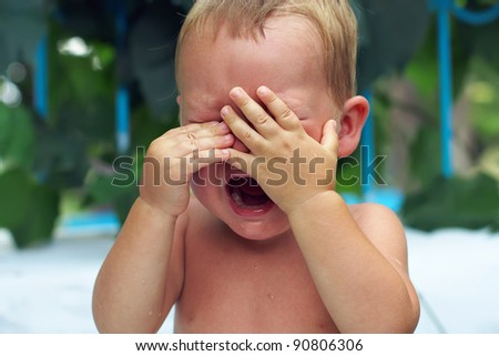 close-up of upset little baby boy crying outdoors - stock photo