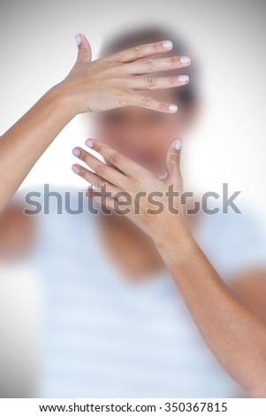 Close-up of upset woman covering face with hands against white background with vignette