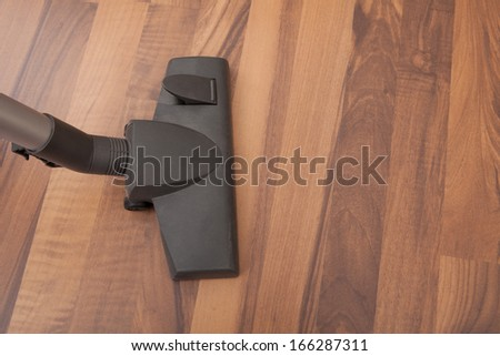 Close-up Of Vacuum Cleaner Cleaning Hardwood Floor - stock photo
