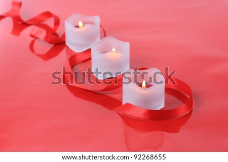 Close-up of valentine candles with ribbon isolated on  red background - stock photo