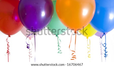 Close up of variety of balloons with ribbons brightly lit - stock photo