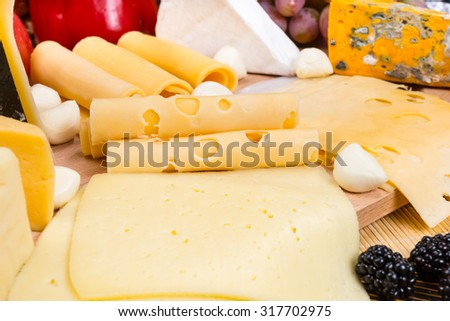 Close Up of Variety of Cheeses Garnished with Fresh Fruit - Detail of Gourmet Cheese Board Appetizer - stock photo