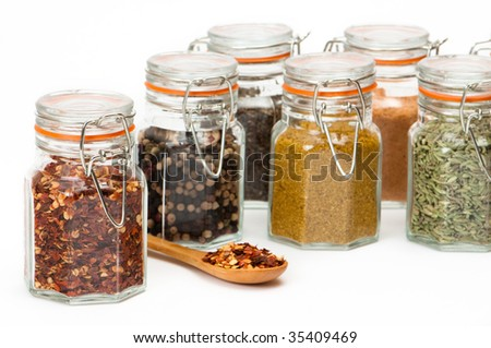 Close up of various colorful glass jars containing various herbs and spices - stock photo