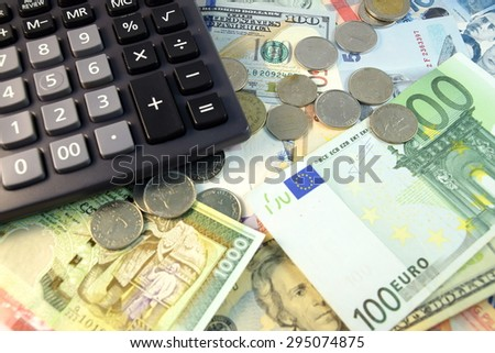 Close up of  Various currency notes and coins from different countries, calculator and gold