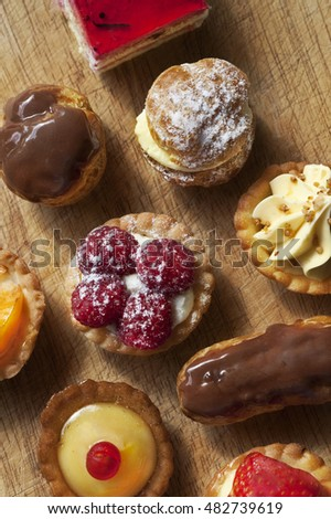 Close up of various French cakes on a wooden board