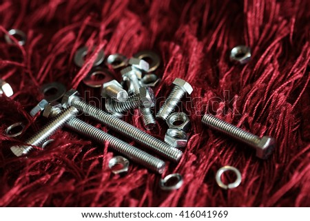 Close-up of various steel nuts and bolts on red carpet - stock photo