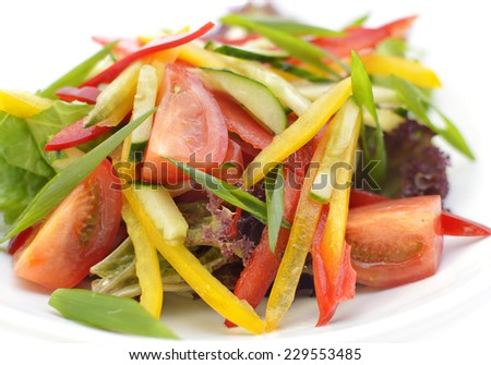 Close up of vegetable mix salad, appetizer. Delicious vegan salad (pepper, tomato, cucumber, lettuce) served in white plate - stock photo
