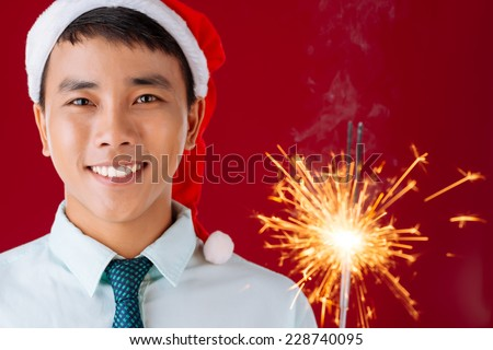 Close-up of Vietnamese man with Bengal light looking at the camera - stock photo