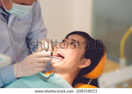Close-up of Vietnamese woman having her teeth examined by specialist - stock photo
