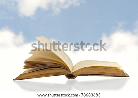 close up of vintage book on blue sky with clouds