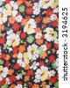 Close-up of vintage fabric with colorful flowers printed on polyester. - stock photo