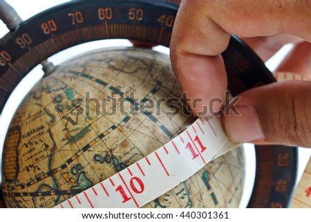 close up of vintage global map with measuring tape around - stock photo