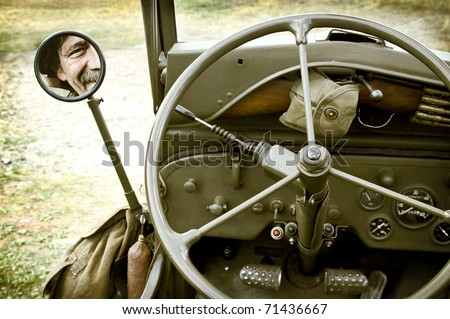 Close up of vintage jeep Willys with man face in mirror - stock photo