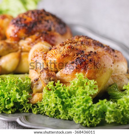 Close up of Vintage metal dish with two whole grilled chicken and green salad over white wooden table. Square image with selective focus - stock photo