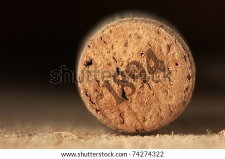 Close-up of vintage wine cork on old wooden surface. - stock photo