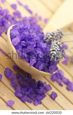 Close-up of violet bath salt in wooden spoon and twigs of lavender on wooden surface. - stock photo