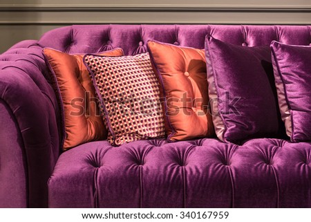 Close up of violet velvet sofa and cushions with vintage style. - stock photo