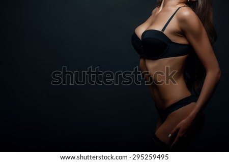 Close up of waist of beautiful girl showing her black underwear. She is posing confidently. Isolated on black background and there is copy space in left side - stock photo