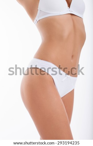 Close up of waist of healthy woman presenting her slim figure. She is in white underwear. Isolated on white background
