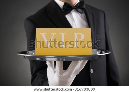 Close-up Of Waiter Showing Vip Text On Banner - stock photo
