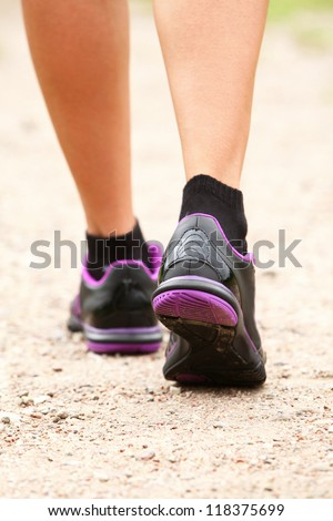 Close up of walking legs in shoes on the road - stock photo